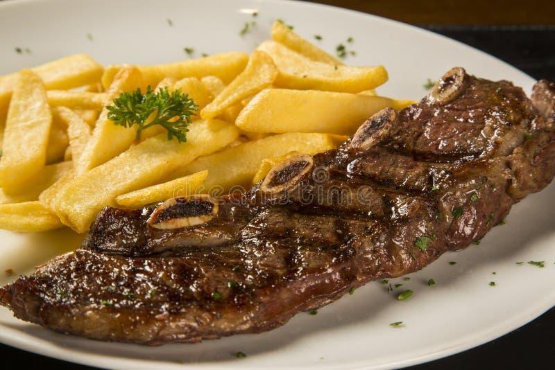 Grillat kött med pommes frites royaltyfria bilder