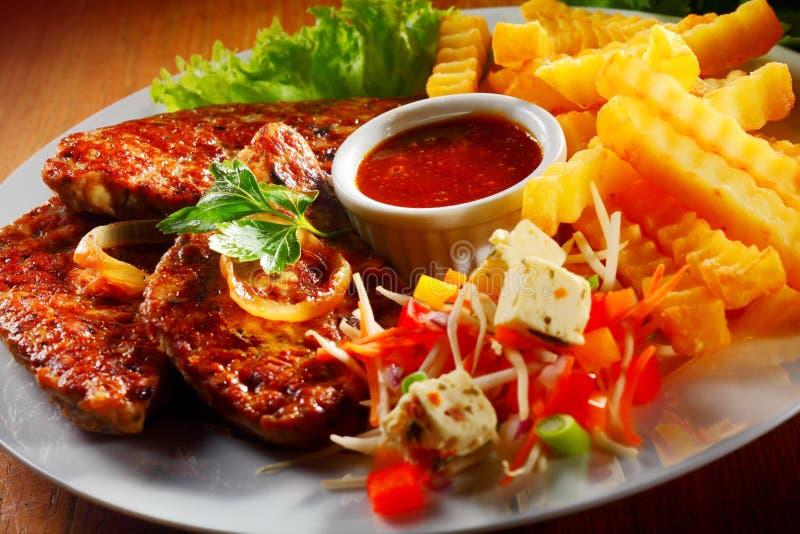 Grillat kött med småfiskar och Veggies på plattan arkivfoto