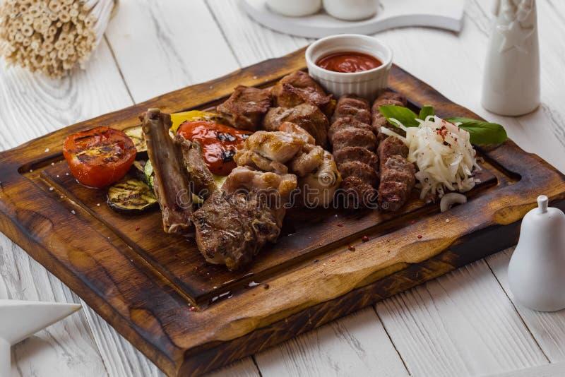 Grillat kött med tomaten, löken och sås fotografering för bildbyråer