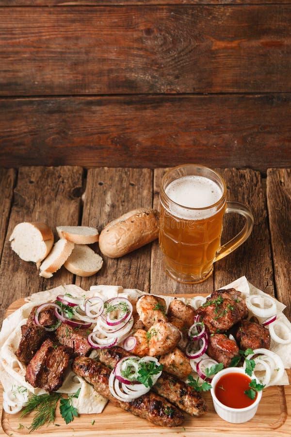 Grillat kött tjänade som med öl på den lantliga tabellen royaltyfri fotografi