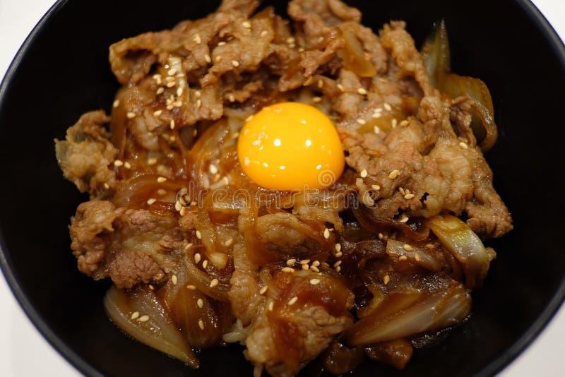 Grillat nötkött med rå äggula över ris arkivbilder