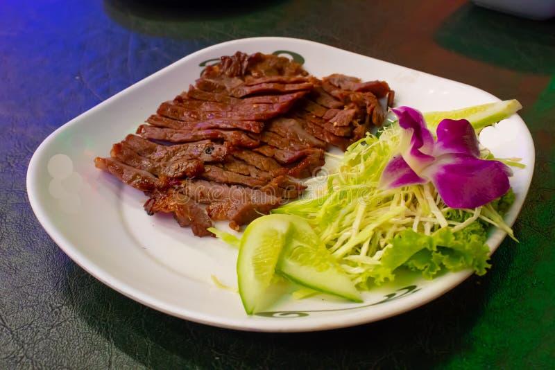 Grillat nötkött på en vit platta med såsen och grönsakerna arkivbilder