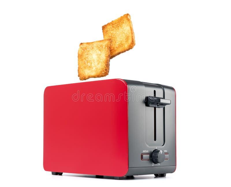 Grillat rostat brödbröd som poppar upp av den röda brödrosten, isolerat på vit bakgrund Mappen inneh?ller en bana till isolering arkivfoto
