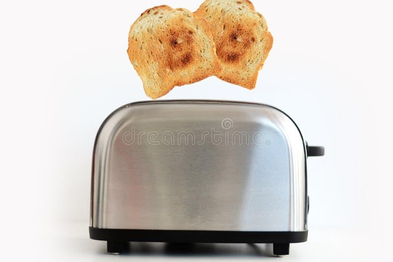Grillat rostat brödbröd som poppar upp av rostfritt stålbrödrosten arkivfoton