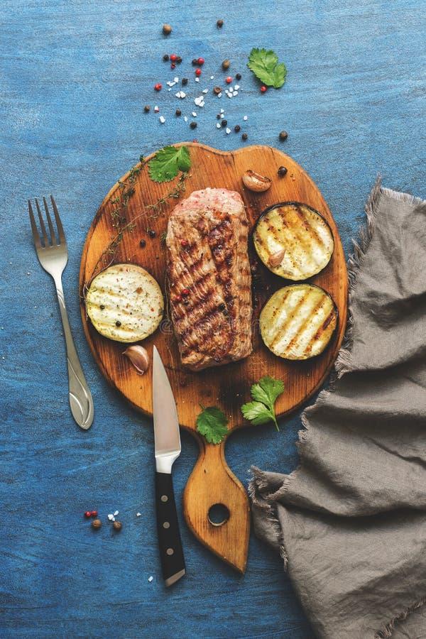 Grillat sällsynt för nötköttköttmedel på en skärbräda med kryddor, blå lantlig bakgrund Bästa sikt, kopieringsutrymme arkivbilder