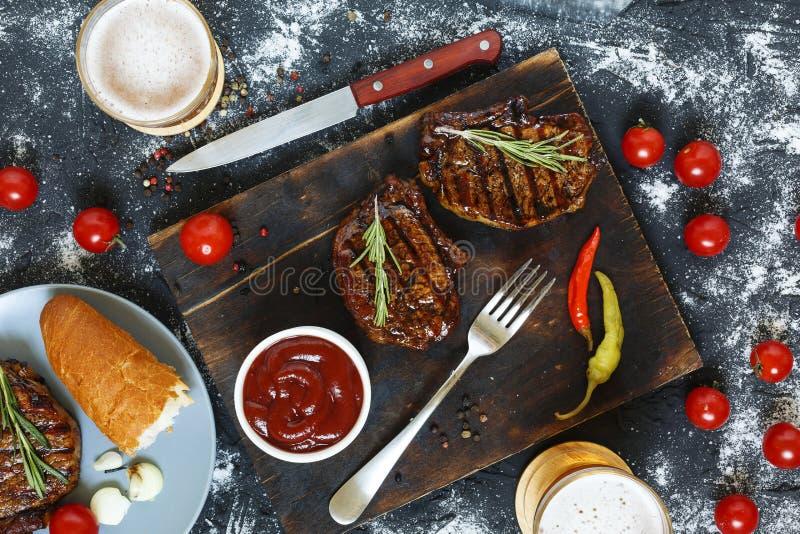 Grillat svart, Angus, biff, tomater, bästa sikt, vitlök, chimichurrisås, kött, skärbräda, bästa sikt royaltyfri foto