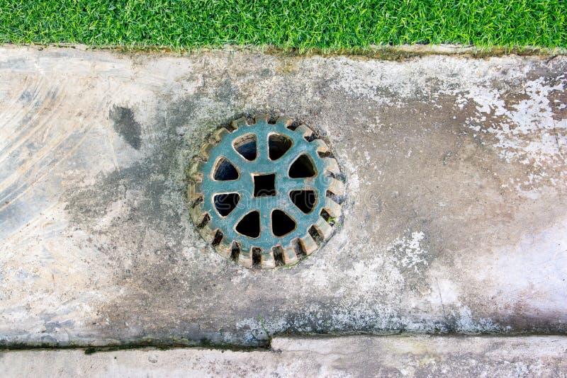 Grille d'égout sur le plancher en béton de drain Drain obstrué de rue Couverture d'?gout Couverture d'?gout en m?tal photo libre de droits