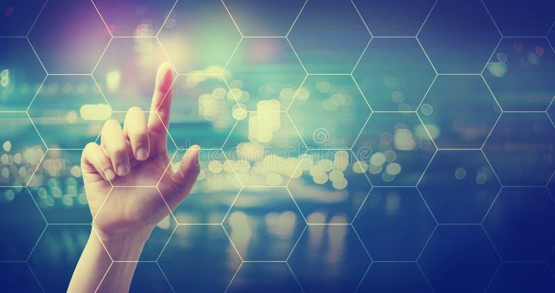 Grille d'hexagone avec la main appuyant sur un bouton photos stock