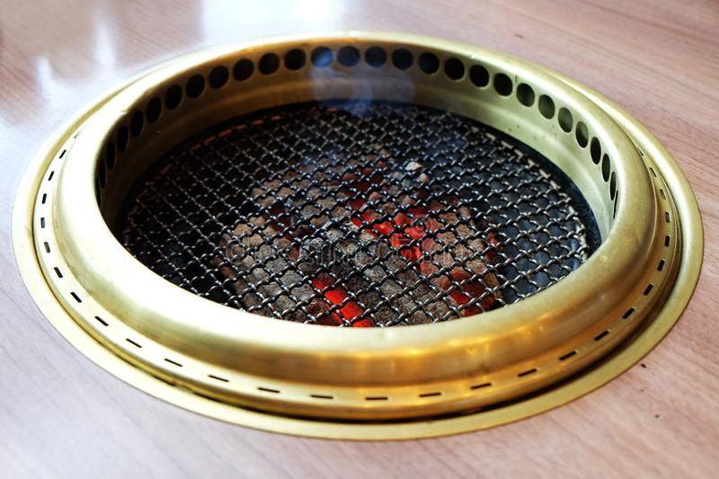 Grille on stove with the charcoal on fire below royalty free stock images