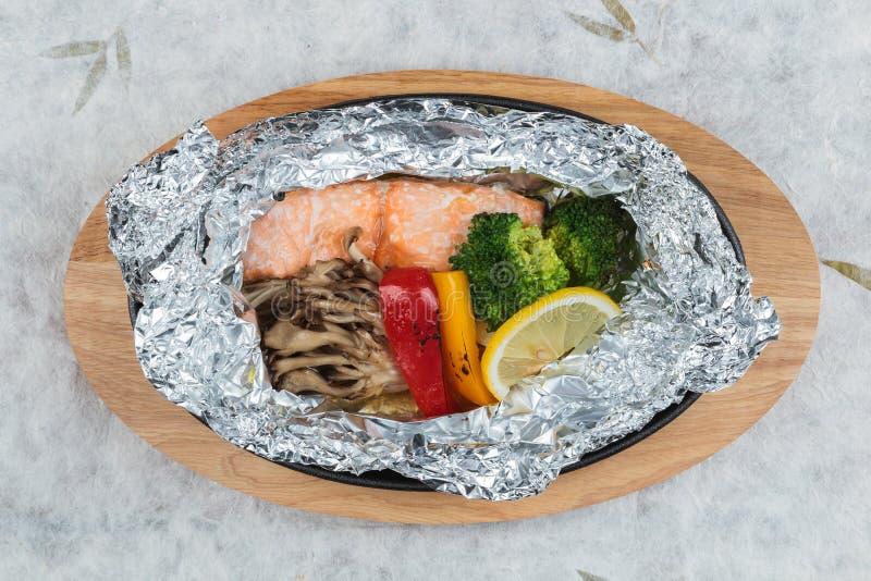 Grilled三文鱼顶视图在箔的包装用硬花甘蓝、甜椒、蘑菇和切片柠檬 免版税库存照片