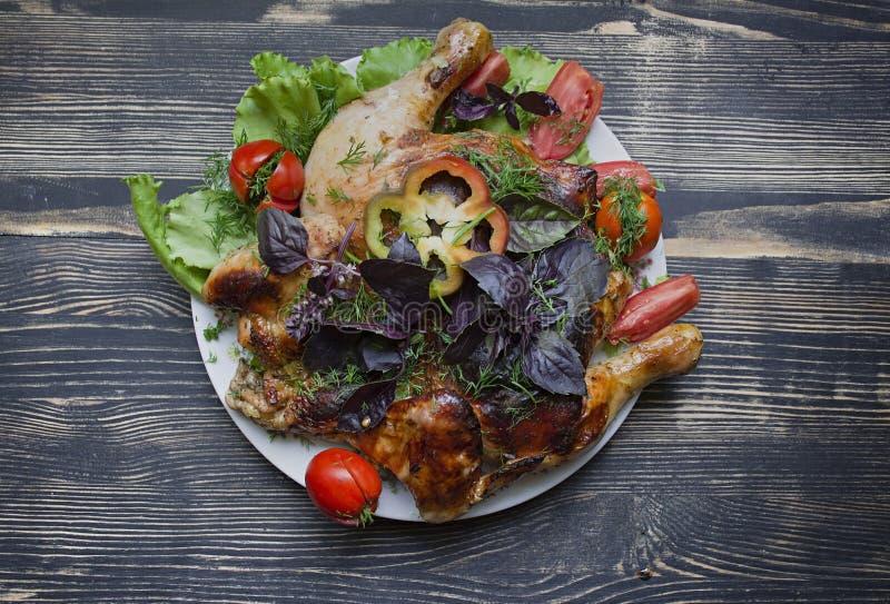 Grilled油煎了在煎锅的烧鸡Tabaka在木背景 库存图片