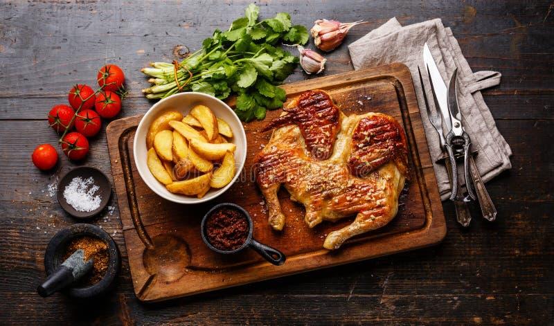 Grilled油煎了烤鸡Tabaka和土豆楔子 库存照片