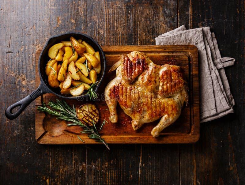 Grilled油煎了烤鸡Tabaka和土豆楔子 免版税库存照片