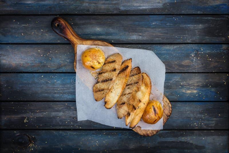 Grilled провозглашать хлеб на разделочной доске стоковое изображение rf