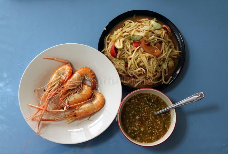 Grilled сварило креветку в белом блюде с соусом в салате шара и папапайи в черном блюде стоковые изображения