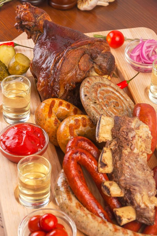 Grilled appetizing sausages on platter. Octoberfest traditional food. Tasty grilled sausages, german food. Delicious stock photography