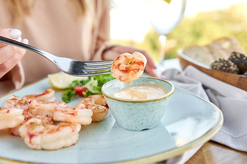 Grilled Argentine shrimp with mango-jalapeno sauce. Lunch in a restaurant, a woman eats delicious and healthy food royalty free stock photography