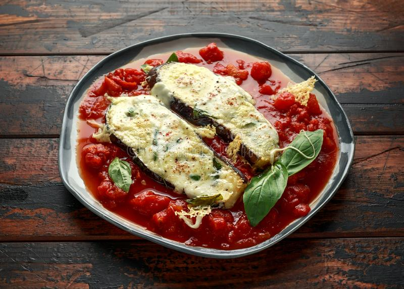 Grilled aubergine, eggplant topped with parmesan cheese crust on crashed tomatoes. Vegetarian pizza version.  stock images