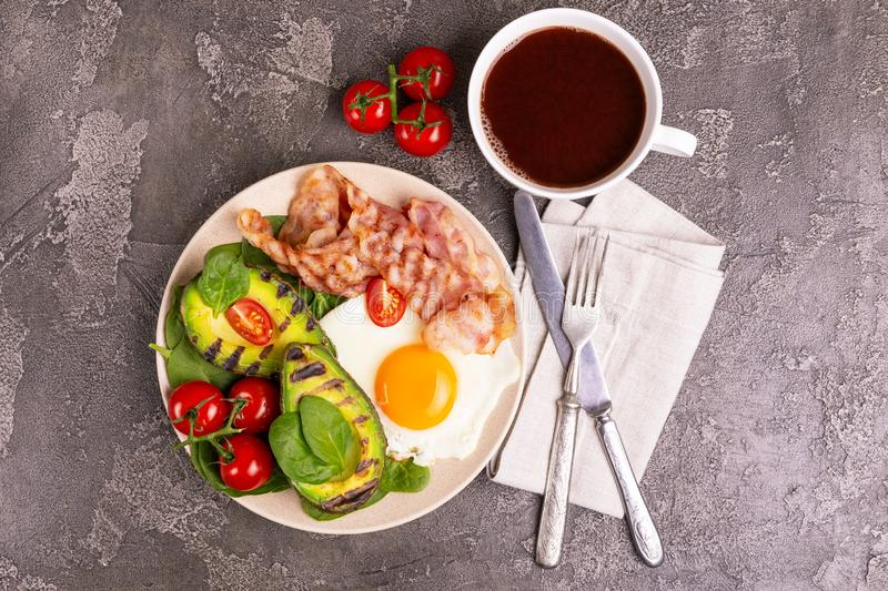Ketogenic diet. Low carb high fat breakfast. Healthy food concept. Grilled bacon and avocado, fried eggs with spinach and cherry tomatoes on gray concrete royalty free stock image