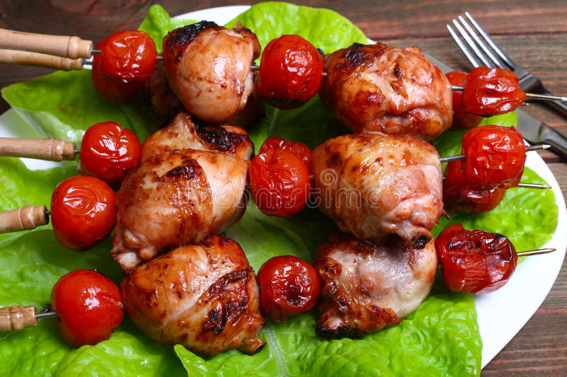 Grilled barbecue kebab chicken legs and tomatoes on skewers.  stock images