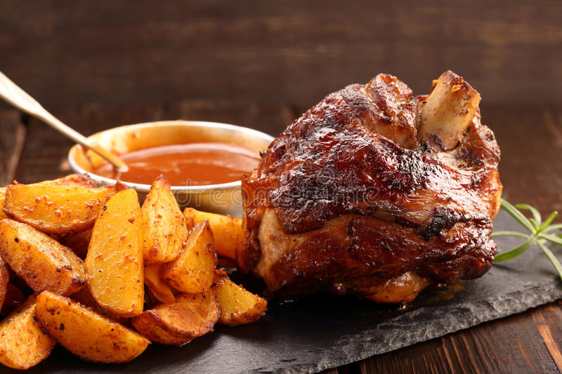 Grilled barbecue meat with baked potato and dip.  stock photos