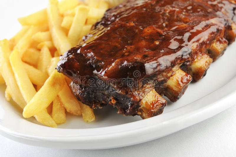 Grilled barbecue ribs. Grilled juicy barbecue pork ribs in a white plate with fries royalty free stock images