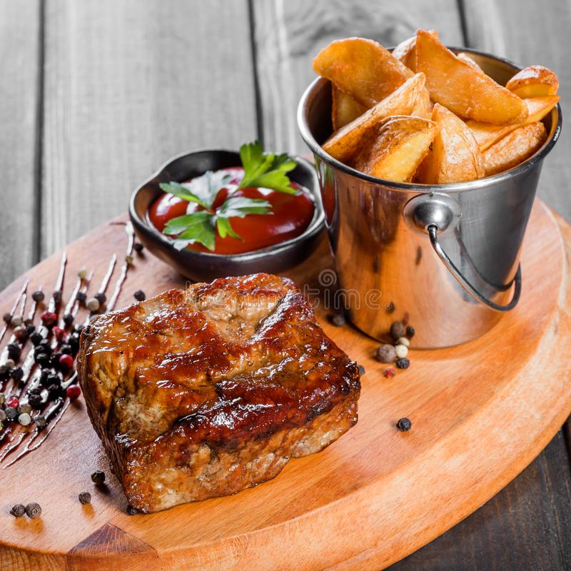 Grilled beaf steak with sauce and potatoes fries in a bucket on wooden cutting board.  stock photos