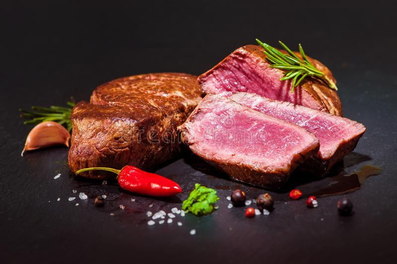 Grilled beef fillet steaks mignon. With spices on dark background royalty free stock image