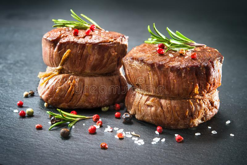 Grilled beef fillet steaks mignon. With spices on dark background royalty free stock photography