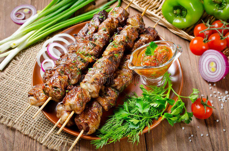 Grilled beef liver kebabs on a dark wooden background stock photos