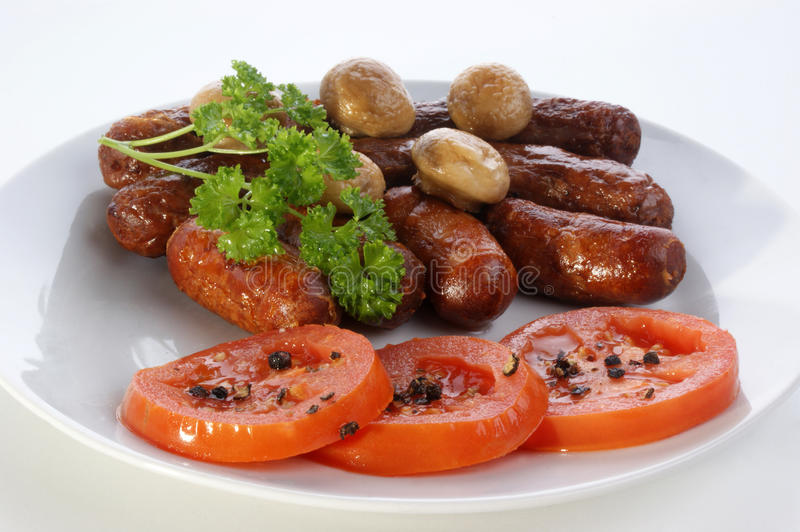 Grilled beef sausages and tomato stock photo