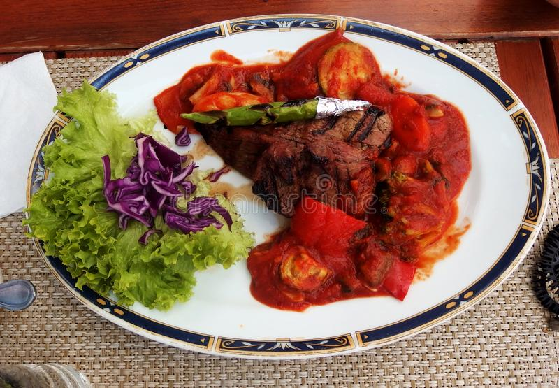 Grilled beef steak with asparagus, lettuce,red cabbage and tomato sauce stock image