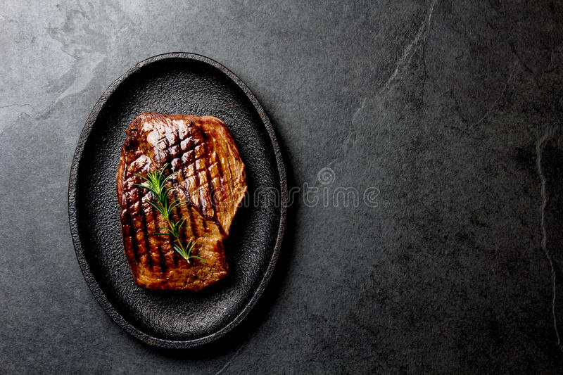 Grilled beef steak on black cast iron plate. Background with copy space. Barbecue, bbq meat beef tenderloin. Top view royalty free stock image