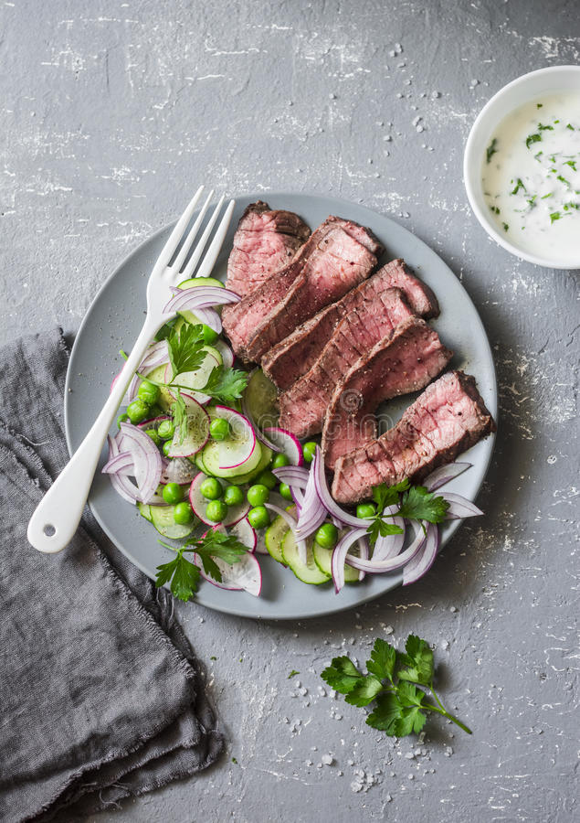 Grilled beef steak and green peas, radish, cucumber salad on a gray background, top view. Healthy food royalty free stock images