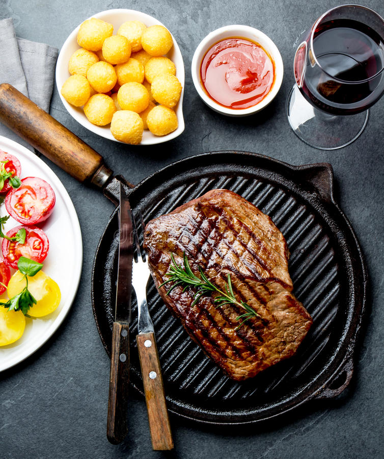 Grilled beef steak on grill pan served with tomato salad, potatoes balls and wine. Barbecue, bbq meat beef tenderloin. Top view, slate background stock image