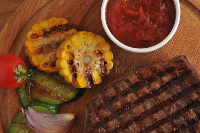Grilled beef steak, grilled vegetables - zucchini, corn, onion royalty free stock photography