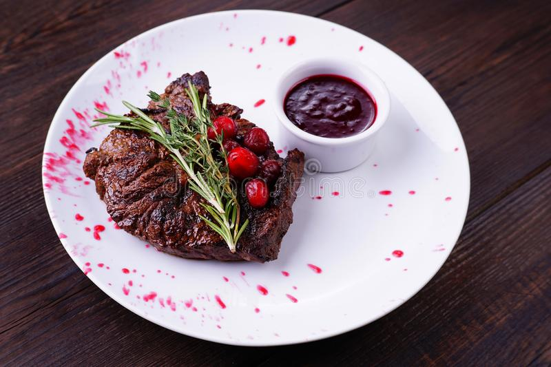 Grilled beef steak with herbs and berry sauce. royalty free stock photo