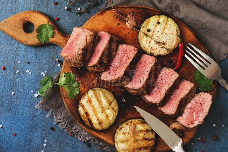 Grilled beef steak medium rare is sliced on a cutting board with spices and baked eggplants. Top view, flat lay. Toned stock images
