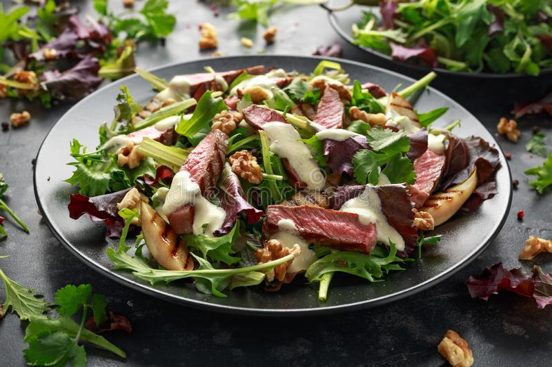 Grilled Beef Steak salad with pears, walnuts and greens vegetables and blue cheese sauce. healthy food. Grilled Beef Steak salad with pears, walnuts and greens stock photography