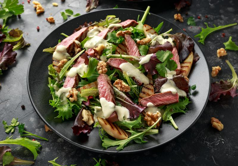 Grilled Beef Steak salad with pears, walnuts and greens vegetables and blue cheese sauce. healthy food. Grilled Beef Steak salad with pears, walnuts and greens royalty free stock photo