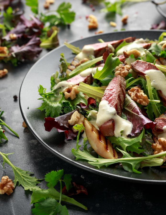 Grilled Beef Steak salad with pears, walnuts and greens vegetables and blue cheese sauce. healthy food. Grilled Beef Steak salad with pears, walnuts and greens royalty free stock photography