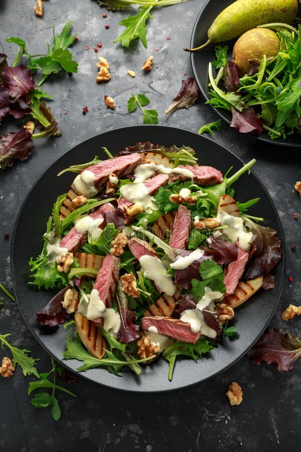 Grilled Beef Steak salad with pears, walnuts and greens vegetables and blue cheese sauce. healthy food. Grilled Beef Steak salad with pears, walnuts and greens stock images
