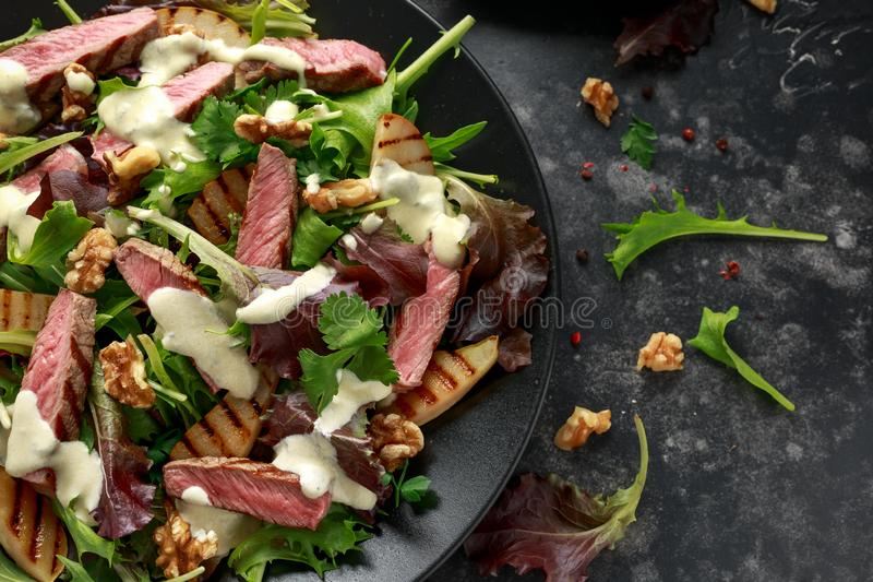 Grilled Beef Steak salad with pears, walnuts and greens vegetables and blue cheese sauce. healthy food. Grilled Beef Steak salad with pears, walnuts and greens stock photos