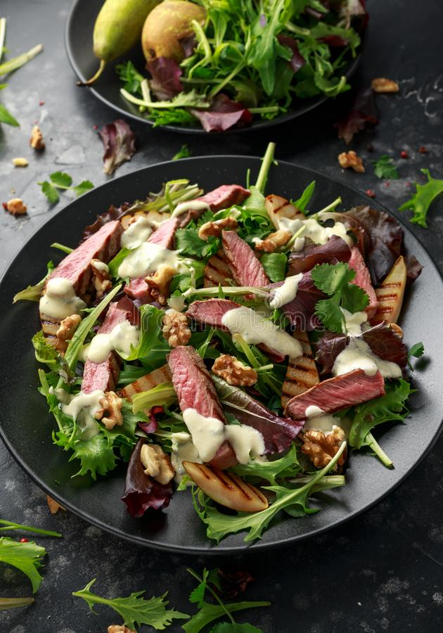 Grilled Beef Steak salad with pears, walnuts and greens vegetables and blue cheese sauce. healthy food. Grilled Beef Steak salad with pears, walnuts and greens stock image