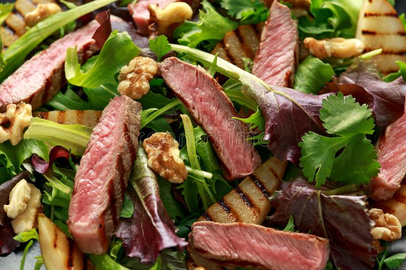 Grilled Beef Steak salad with pears, walnuts and greens vegetables and blue cheese sauce. healthy food. Grilled Beef Steak salad with pears, walnuts and greens royalty free stock images