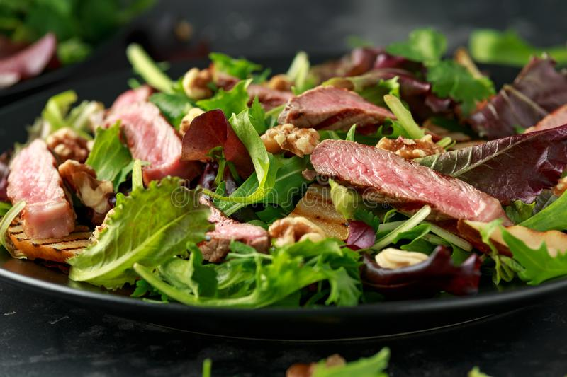 Grilled Beef Steak salad with pears, walnuts and greens vegetables and blue cheese sauce. healthy food. Grilled Beef Steak salad with pears, walnuts and greens stock photo