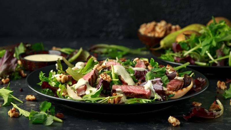 Grilled Beef Steak salad with pears, walnuts and greens vegetables and blue cheese sauce. healthy food. Grilled Beef Steak salad with pears, walnuts and greens royalty free stock photos