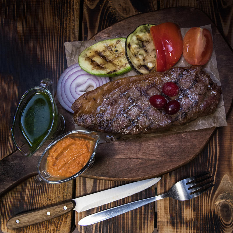 Grilled beef steak. With sauce and vegetables royalty free stock photography
