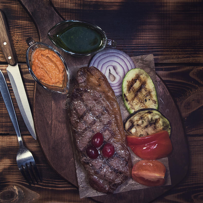 Grilled beef steak. With sauce and vegetables stock photos