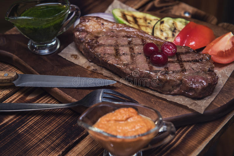 Grilled beef steak. With sauce and vegetables royalty free stock image